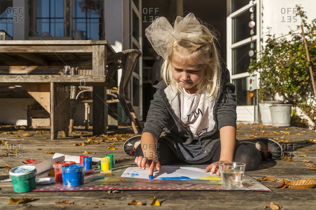 Blond little girl painting with finger colors on the terrace