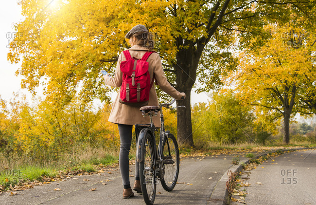 Young woman with backpack pushing her bicycle in autumn landscape