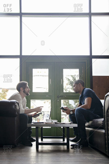Two men with portable devices sitting on couch in a lounge