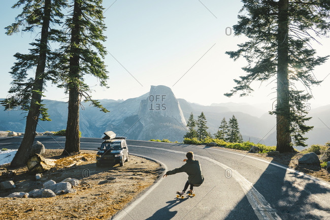 Man skateboarding on curved road in Yosemite National Park
