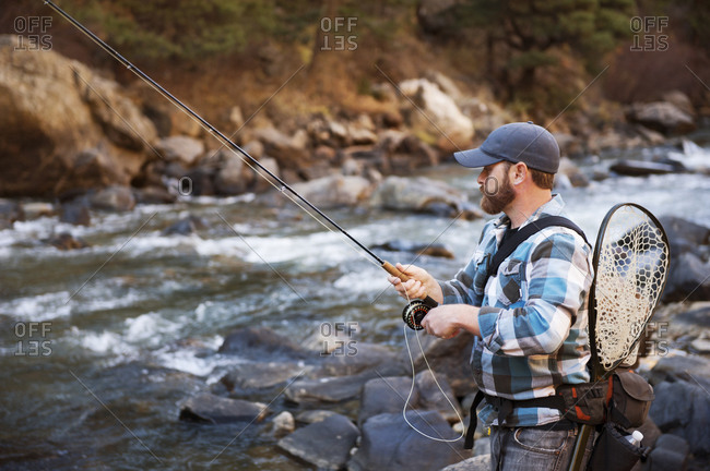 Man with gear fishing in river with gear