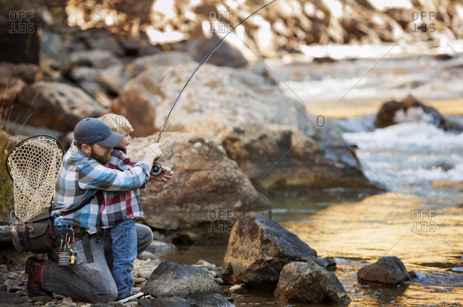 Man helping a boy fish in river