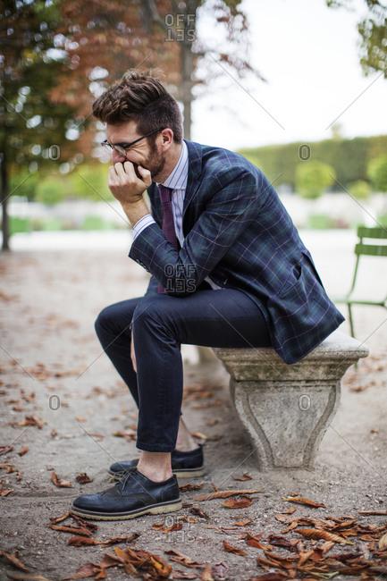 Stylish man on Parisian park bench