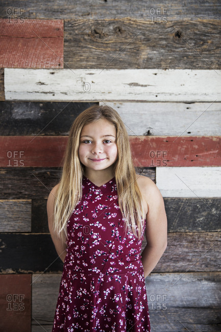 Girl by reclaimed wood wall