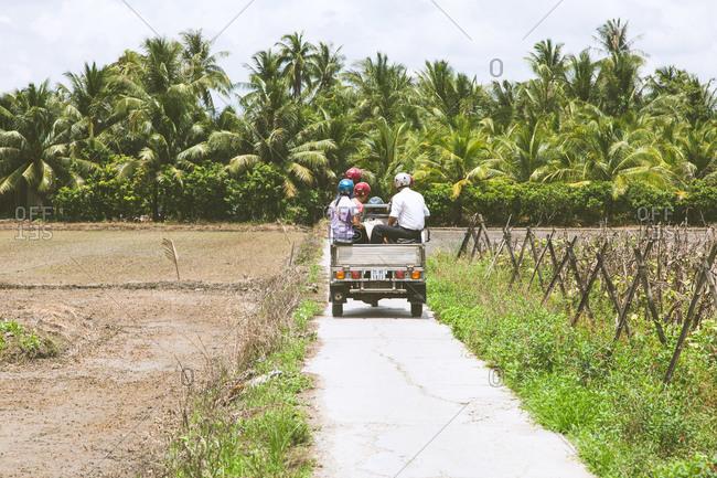 Tourists travel through the Vietnamese countryside in a tuk tuk