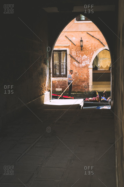 Venice, Italy - June 7, 2014: Gondola passes by an archway