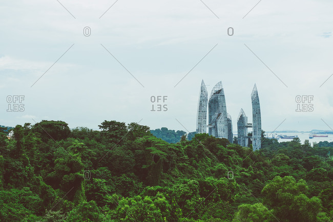 Singapore - August 12, 2014: Modern glass building rising through trees in Singapore