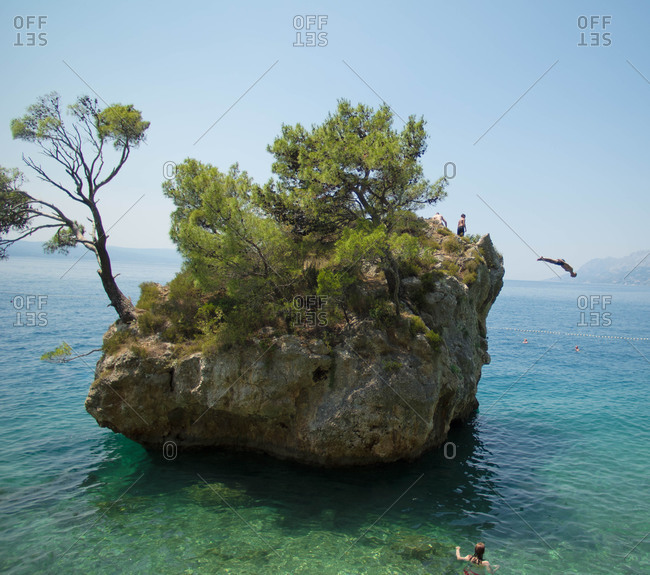 Person diving off a rock island