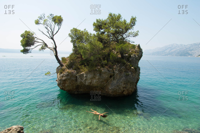 Woman swimming by a rock island