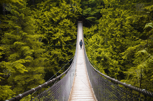 Woman walking on a hanging bridge