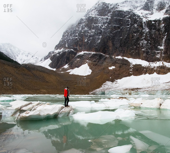Man standing on ice in mountain lake