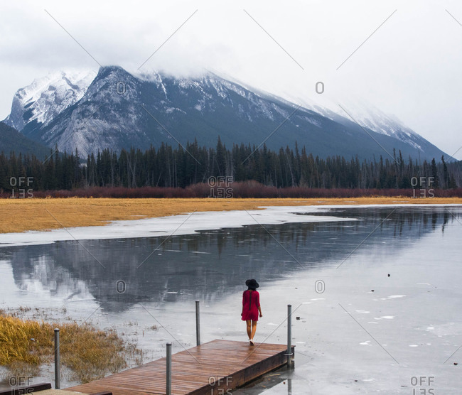 Woman on dock overlooking mountain lake