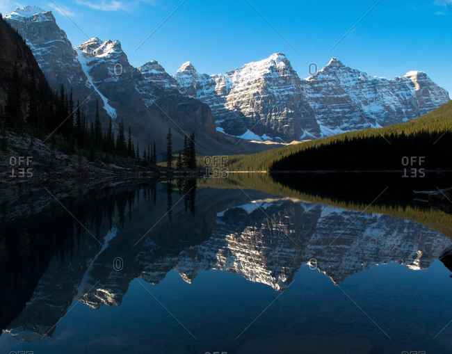 Snowy mountain range reflected in still lake