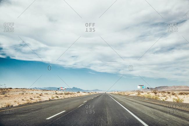 Empty desert highway under a cloudy blue sky