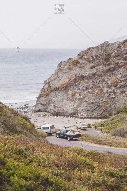 Vehicles parked near a rocky beach access