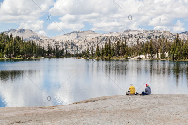 Hikers resting beside a mountain lake