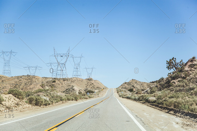 Empty highway and electric towers in the hills
