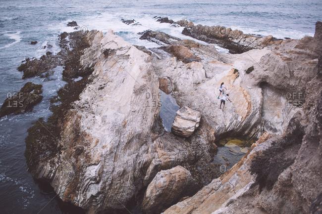 Couple climbing boulders near a seaside