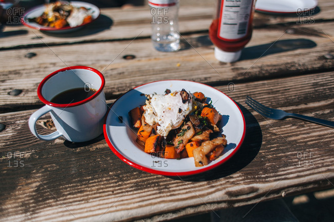 Camping breakfast on a rustic wooden picnic table