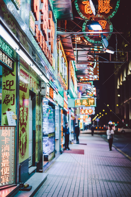 Storefronts and street at night in Macau