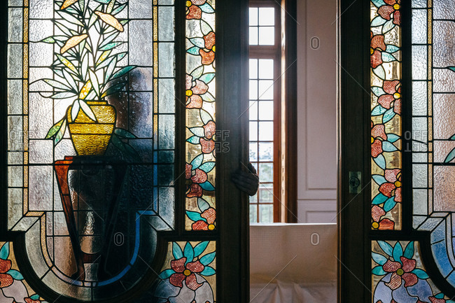 Man opening sliding stained glass doors