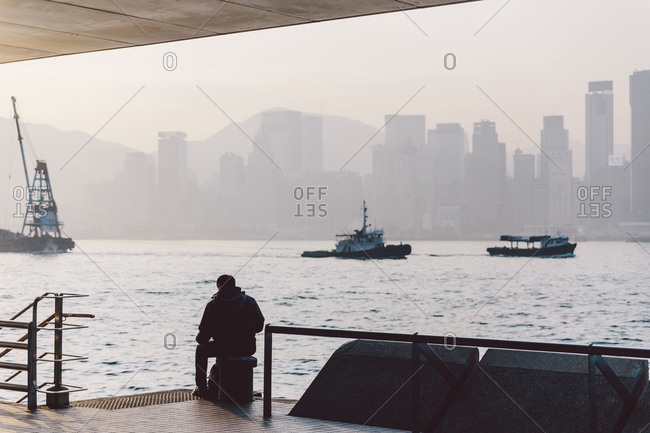 Man waiting at ferry terminal on a foggy morning in Hong Kong