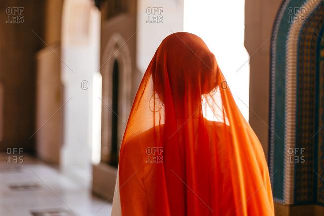 Woman wearing an orange veil in Oman