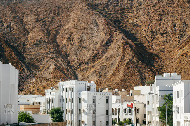 Steep rock mountains rise above city of Muscat, Oman