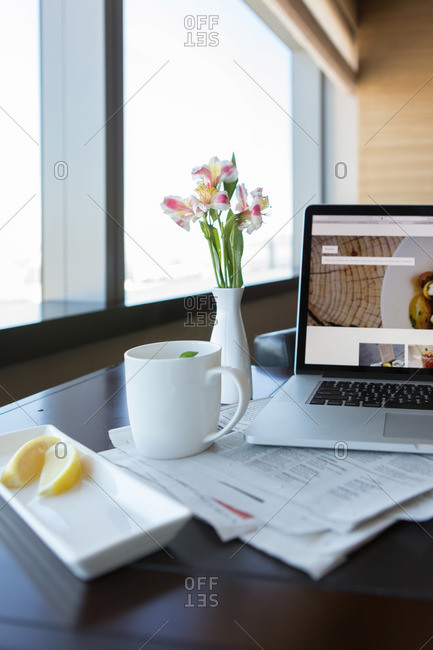 Mug of tea with lemon and laptop computer set on hotel room table