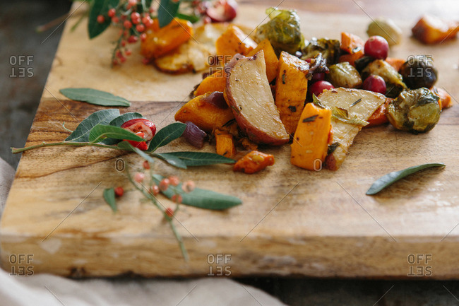 Roasted potatoes, squash and Brussels sprouts with sage on wooden cutting board