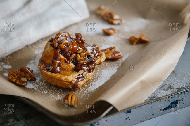 Close-up of maple sticky bun with pecans on baking tray