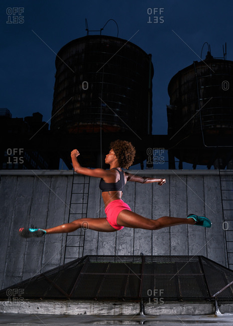 Athletic dancer leaping on a rooftop