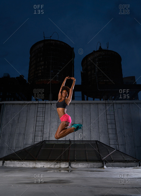 Athletic dancer jumping on a rooftop