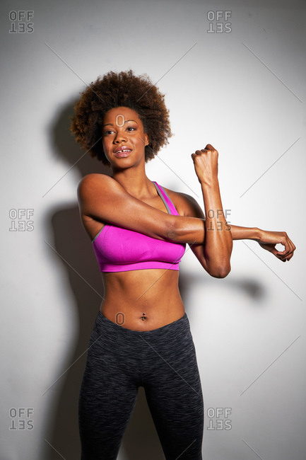 Young athletic woman stretching her arms