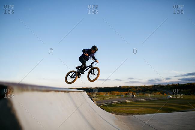 Boy in midair bike ramp jump