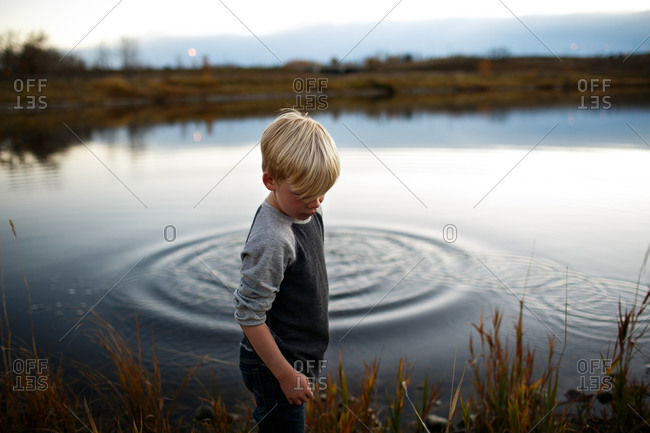 Boy by lake with ripples