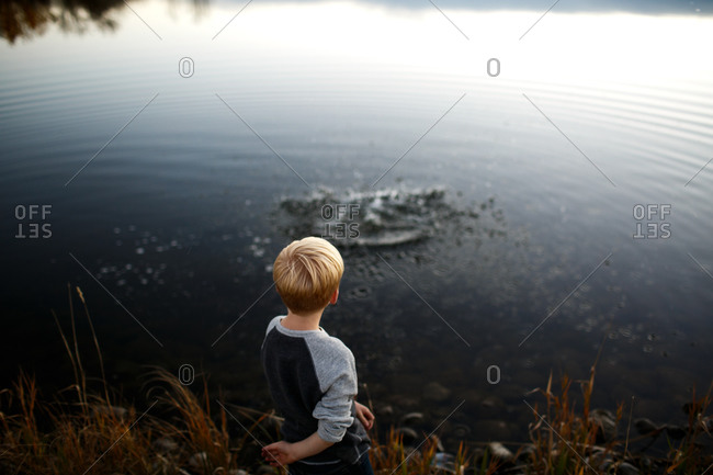Boy making ripples in lake