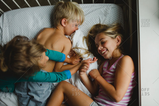 Three young siblings playing together on bed