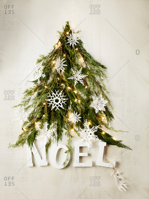 The word NOEL at the base of a tree made of pine boughs
