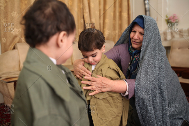 Tehran, Iran - January 23, 2015: A mother of martyr putting her son's clothes on her grandson