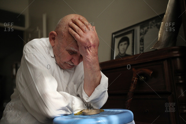 A father of martyr sitting at home, holding his head