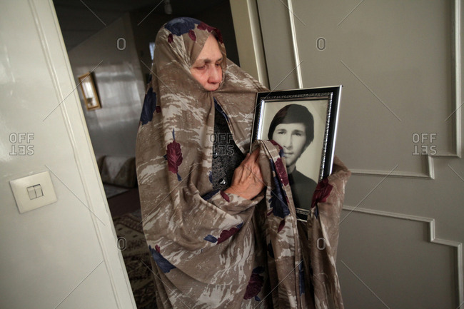 Tehran, Iran - February 25, 2014: A mother of martyr cleaning a picture of her son