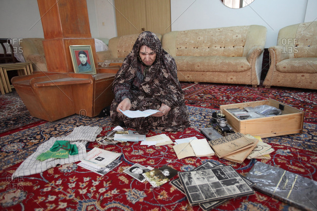 Tehran, Iran - February 27, 2014: A mother of martyr looking at a pictures of her son