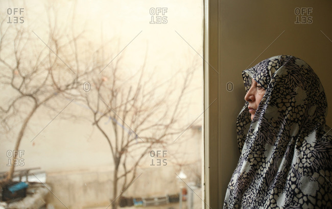 Tehran, Iran - February 6, 2015: An Iranian woman at home looking out a window