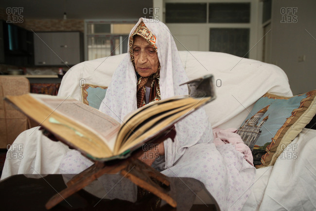 Tehran, Iran - September 25, 2014: An old woman reading Quran at home