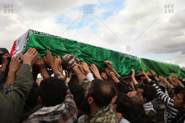 Ahwaz, Iran - March 11, 2014: People holding coffin during an Iranian martyr funeral