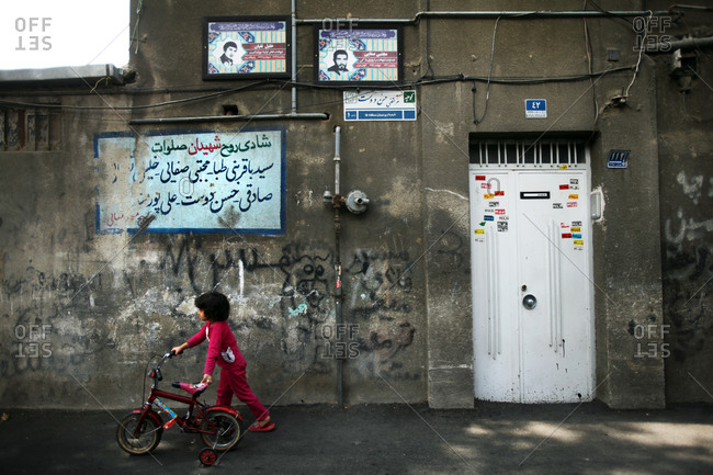 Little girl with her bicycle on the street in Iran