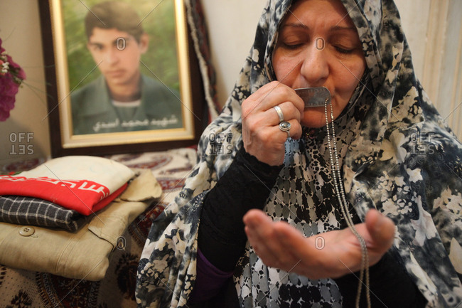 Tehran - June 11, 2015: Mother of martyr kissing her son's number tag