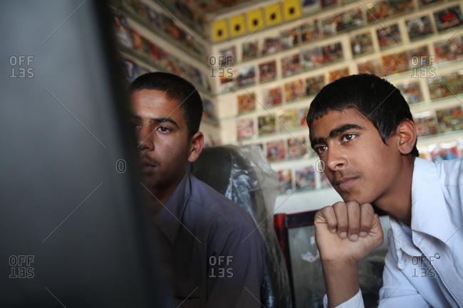 Zabol, Iran - May 1, 2014: Two boys watching a computer screen
