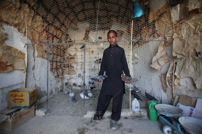 Zabol, Iran - May 1, 2014: Boy holding two birds